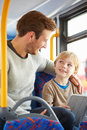 Son using digital tablet on bus journey with father whilst smiling at each other Royalty Free Stock Photo
