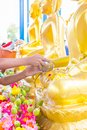 Songkran festival in Thailand, Hand woman use the water pouring to golden buddha statue. Royalty Free Stock Photo