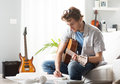 Songwriter composing a song young man playing guitar and sitting on sofa Stock Image