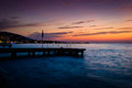 Soothing serene haven sunset on the by the seaside with dockage made of stone where people go swimming and fishing Royalty Free Stock Photo