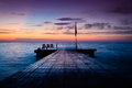 Soothing serene haven sunset on the by the seaside with dockage made of stone where people go swimming and fishing Royalty Free Stock Image