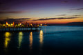 Soothing serene haven sunset on the by the seaside with dockage made of stone where people go swimming and fishing Stock Image