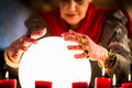Soothsayer during a seance or session with crystal ball female fortuneteller esoteric oracle sees in the future by looking into Royalty Free Stock Photography