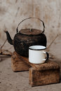Sooty old teapot and white enamel mug on small wooden bench Stock Image