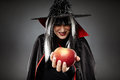 Sorcerer offering a poisoned apple tricky witch halloween theme Royalty Free Stock Images