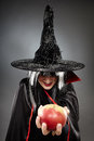 Sorcerer offering a poisoned apple tricky witch halloween theme Stock Photo