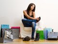 Sore feet from shopping photo of a young beautiful female sitting on a chair surrounded by bags and rubbing her Stock Photo