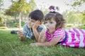 Sorella enjoying their lollipops del bambino e del giovane fratello all aperto Immagine Stock