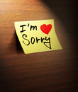 Sorry handwritten on yellow note paper Stock Photos