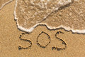 SOS - word drawn on the sand beach Royalty Free Stock Photo