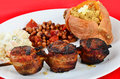 Soul food dinner upscale with skewered pork tenderloin wrapped in bacon and grilled to perfection with baked sweet potato and Stock Images