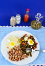 Soul food supper collard greens seasoned with bacon drippings and salt pork and garnished with boiled egg on white plate with Royalty Free Stock Images