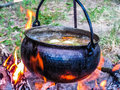 Soup cooking in a copper kettle on the fire making medieval warm food at camp Royalty Free Stock Photography