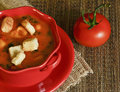 Soup with croutons and a tomato Stock Photos