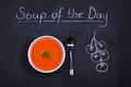 Soup of the day chalkboard advertising with a bowl tomato and spoon garnished with parsley widh chalk drawn tomatoes Stock Image