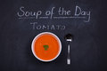 Soup of the day chalkboard advertising tomato as with a bowl tomato and spoon garnished with parsley Stock Images