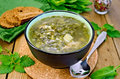 Soup green of sorrel and nettles with bread on the board nettle spinach in a bowl spoon pepper against a wooden Royalty Free Stock Photography