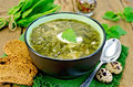 Soup green sorrel and nettles with a spoon of nettle spinach in bowl bread pepper quail eggs on wooden board Royalty Free Stock Photography
