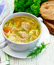Soup with meatballs and noodles in bowl on light board Royalty Free Stock Photo