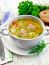 Soup with meatballs and noodles in white bowl on board Royalty Free Stock Photo
