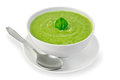 Soup puree with spinach in bowl and spoon cream green from a white leaf on a plate a light shade on white background Royalty Free Stock Image