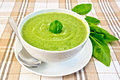 Soup puree with spinach and spoon in bowl cream green from a white saucer leaves on the background fabric Royalty Free Stock Image