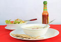 Soup and salad dollop of louisiana hot sauce on bowl of broccoli potato with fresh garden saltine crackers Royalty Free Stock Photography