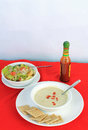 Soup and salad vertical dollop of louisiana hot sauce on bowl of broccoli potato with fresh garden saltine crackers format Royalty Free Stock Photography