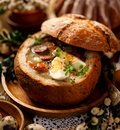 The sour soup Å»urek made of rye flour with smoked sausage and eggs served in bread bowl.