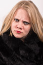 Sour and stubborn young woman in a fur jacket stares into the camera with a white backround behind Stock Photo