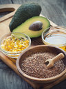Sources of omega fatty acids flaxseeds avocado oil capsules and flaxseed oil Stock Photo