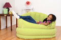 South African child relaxing in green chair Stock Photo