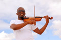 South african musician outdoor portrait of a with black sunglasses and friendly smiling facial expression playing his violin in Royalty Free Stock Photography