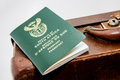 A South African passport next to a vintage travel bag. This image can be used to represent travel or immigration. Royalty Free Stock Photo