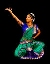 South asian classical dancer young woman in traditional sari dancing indian dance bharatanatyam on a black background Royalty Free Stock Photo