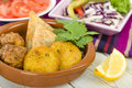 South asian starter selection aloo tikki onion bhaji and vegetable samosas served with lemon wedges salad and dipping sauce Royalty Free Stock Image