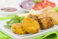 South asian starter selection aloo tikki onion bhaji and vegetable samosas served with lemon wedges salad and dipping sauce Stock Photos