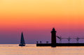 South haven twilight a vividly colorful sky silhouettes a sailboat people and the lighthouse at michigan on lake michigan Stock Photography