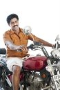 South indian man riding a motorcycle and smiling Royalty Free Stock Photos