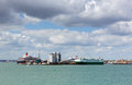 Southampton Docks with big cruise ship and cargo vessel on calm summer day with fine weather blue sky and white clouds Royalty Free Stock Photo