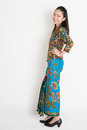 Southeast asian woman full length cheerful female in batik dress standing on plain background Stock Photography