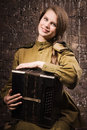 Soviet female soldier in uniform of world war ii with an accordi old accordion Royalty Free Stock Photo