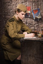 Soviet female soldier in uniform of World War II writes a letter Royalty Free Stock Photo