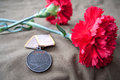 Soviet medal for combat service and two red carnations still life dedicated to victory day may Stock Photos