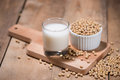 Soy milk or soya milk and soy beans in spoon on wooden table. Royalty Free Stock Photo