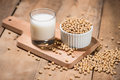 Soy milk or soya milk and soy beans on wooden table. Royalty Free Stock Photo