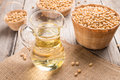 Soybean and soybean oil in jar on wood Royalty Free Stock Photo
