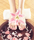 Spa background with beautiful feet, flowers and petals Royalty Free Stock Photo