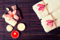 Spa background with shampoo bottles, white towels, tropical flow Royalty Free Stock Photo