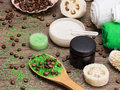 Spa and cellulite busting products on wooden surface anti cosmetics with caffeine spoon with green coarse sea salt coffee beans Royalty Free Stock Image